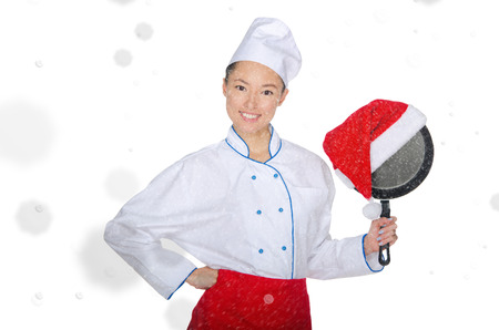 pan asian: happy asian chef with frying pan and Christmas hat in falling snow
