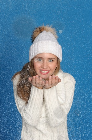 pleasantness: beautiful woman in upper clothes with snow on blue background