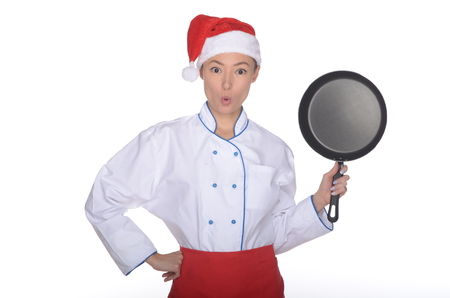 unexpectedness: surprised asian chef with frying pan and Christmas hat isolated in white