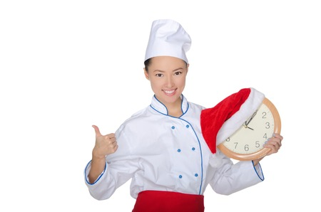 pleasantness: beautiful asian chef with clock and Christmas hat isolated in white