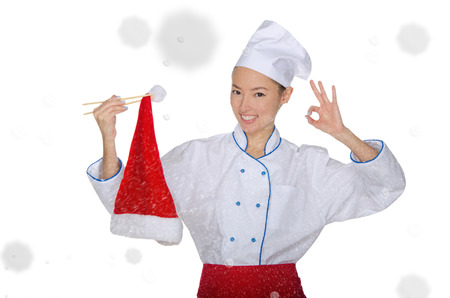 pleasantness: smiling asian chef in christmas cap with chopsticks under snow isolated on white