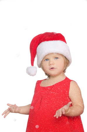 unexpectedness: surprised little girl in christmas cap in snow isolated on white Stock Photo