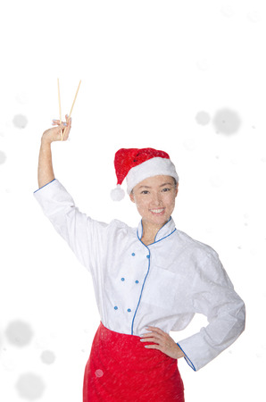 pleasantness: pleased asian chef in christmas outfit with chopsticks under snow isolated on white