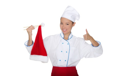 pleasantness: smiling asian chef in christmas cap with chopsticks isolated on white Stock Photo