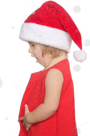 suddenness: surprised child in christmas cap in snow isolated on white
