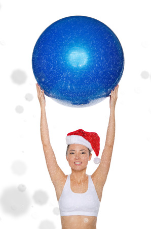 fitball: smiley asian woman in Santa cap holds fitball under snow isolated on white
