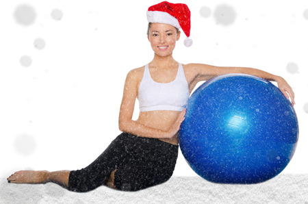 fitball: happy asian woman in christmas cap with fitball under snow isolated on white