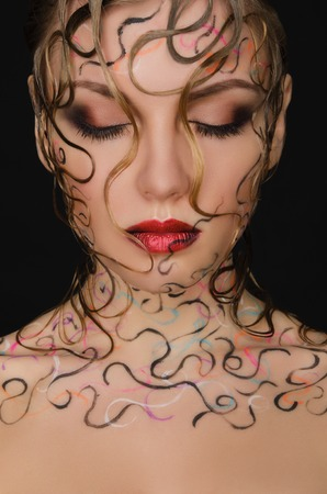 frizz: portrait of beautiful woman with wet hair and face art on black background