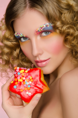 frizz: woman with donut in face on pink background Stock Photo