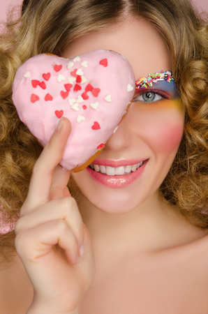 signify: beautiful woman with donut in face on pink background