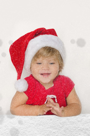 signify: Smiling european girl in Santa suit with snow studio shot