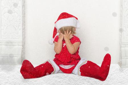 santa suit: Little child in Santa suit sitting on floor with snow studio shot