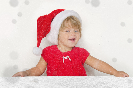 santa suit: Happy girl in Santa suit with snow studio shot
