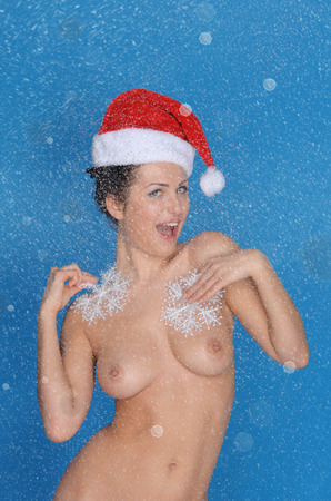 Nude woman in hat Santa with snowflakes on blue background photo