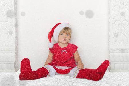 santa suit: Little girl in Santa suit sitting on floor with snow studio shot