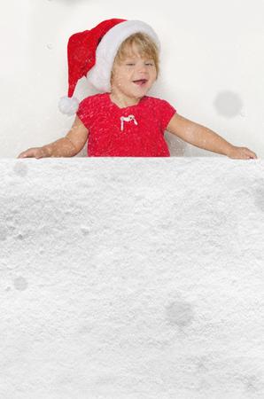 santa suit: Smiling girl in Santa suit with snow studio shot