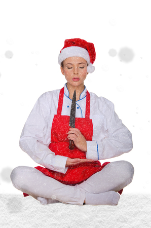 Cook in Santa hat, yoga, knife under snow on white background