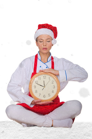 cook in Santa hat, yoga clock under snow on white background Stock Photo