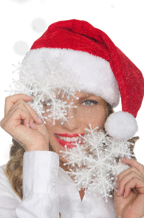 pleasantness: happy woman in Santa hat with snowflakes isolated on white