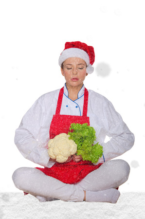 chef in hat of Santa Claus, yoga, vegetables under snow on white background
