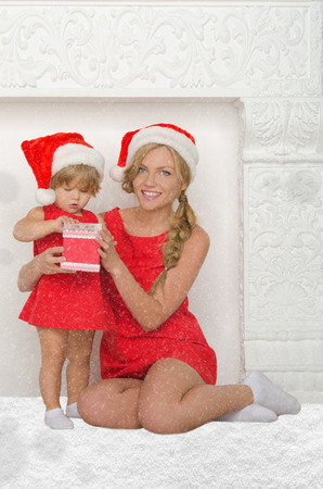 pleasantness: happy mother and daughter dressed as Santa with gift and snow on gray background