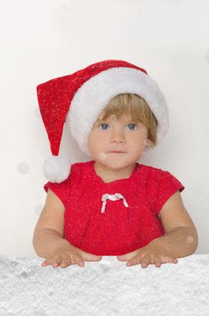 santa suit: girl in Santa suit in falling snow on gray background