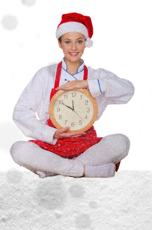 Woman cook in Santa hat, yoga clock under snow on white background