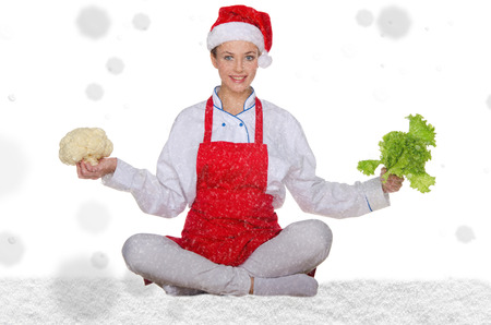 Woman cook in Santa hat, yoga, vegetables under snow on white background Stock Photo