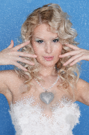 frost winter: beautiful woman with snowflakes on blue background Stock Photo