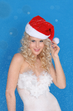 pleasantness: Beautiful woman in Santa hat and snow on blue background