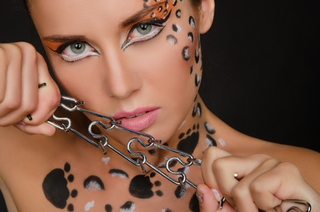 young woman with an animal face art and spines on dark background Stock Photo