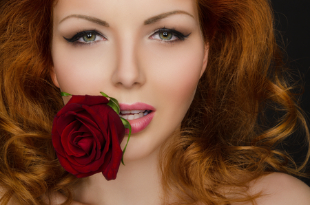 Red rose in the teeth of woman with beautiful hair
