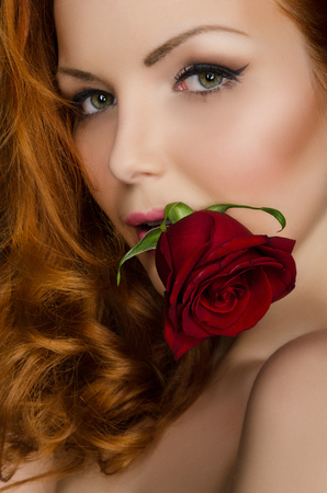 woman with long red hair holds beautiful rose in her mouth