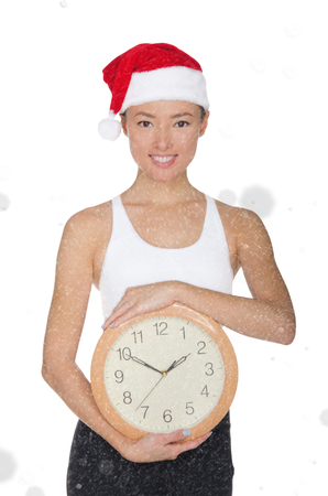 asian women in a Santas hat with a clock isolated on white