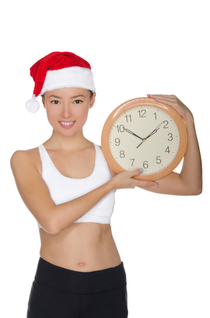happy asian women in a Santas hat with a clock isolated on white Stock Photo