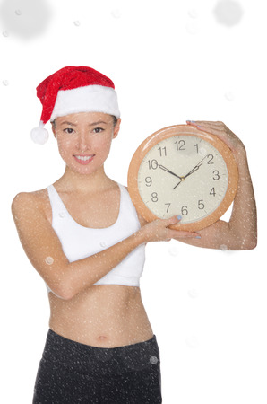 smiling asian women in a Santas hat with a clock isolated on white