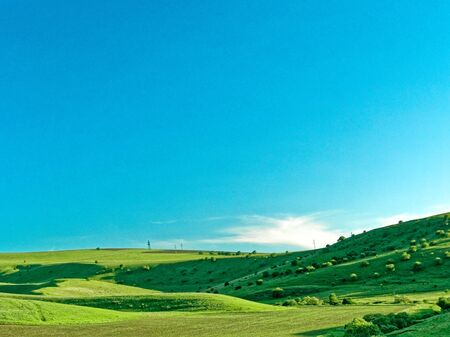 Spring landscape in the mountains. grassy field and hills. rural landscape.
