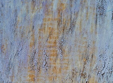 Grunge background is an old multi-colored textured surface. Dilapidated shabby wall of light purple hue, which exfoliate layers of old colors.
