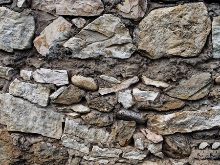 Textured fragment of the granite stone brown-gray facade of the wall. Фото со стока