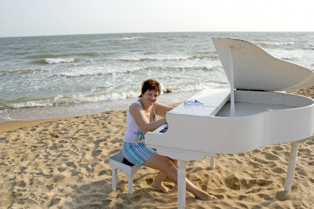 middle-aged woman in clothes for outdoor activities sits behind a white grand piano on the beach photo