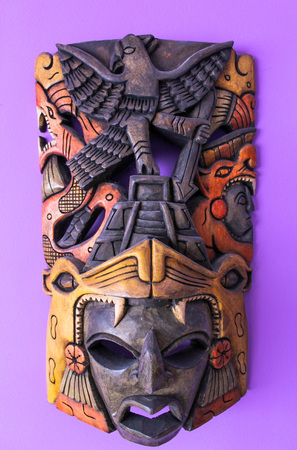 Picture of an african wooden mask on a purple wall Stock Photo