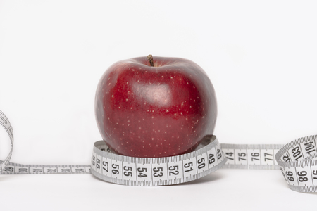 Red apple with measuring tape diet concept isolated on white background