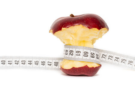 bitten: Healthy bitten red apple with measuring tape isolated on white background