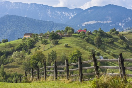 Landscape of Magura village houses and hills with the Carpathian Mountains in the background