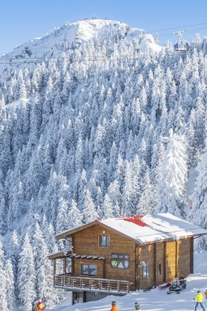 POIANA BRASOV, ROMANIA - JANUARY 24, 2016: Mountain cabin from Poiana Brasov resort with peak and forest covered by snow in winter season