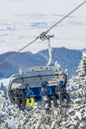 chairlift: POIANA BRASOV, ROMANIA - JANUARY 24, 2016: Tourists in chairlift in winter season going to the ski slope in resort Poiana Brasov, Romania Editorial