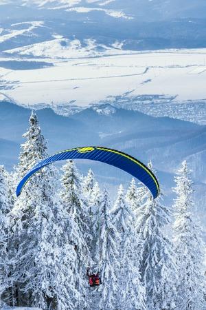 brasov: POIANA BRASOV, ROMANIA - JANUARY 24, 2016: Paragliding instructor taking off the ski slope and flying in tandem over the mountain resort Poiana Brasov in Romania