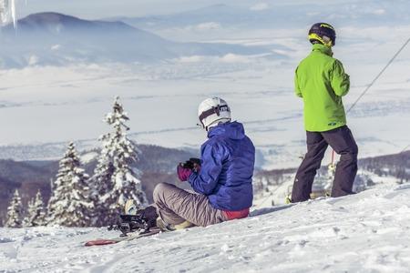 brasov: POIANA BRASOV, ROMANIA - JANUARY 24, 2016: Snowboarders sitting on the sky slope in Poiana Brasov, Romania