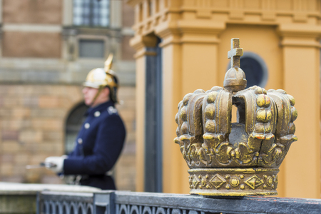 royal guard: Swedish royal crown and soldier Royal Guard blurred in the background at the Royal Palace Square in Stockholm Stock Photo