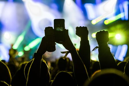 People taking photographs with smart phone during a public music concert with can of beer in hand Stok Fotoğraf - 132224142